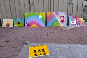 Fünf Bilder stehen in einer Reihe an einer Wand